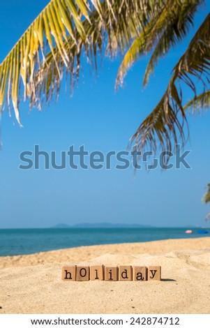 Holiday word on wood rubber stamps stack on the sand beach for vacation and summer season concept, beautiful sea view during daytime on a sunny day with blue sky on background - stock photo