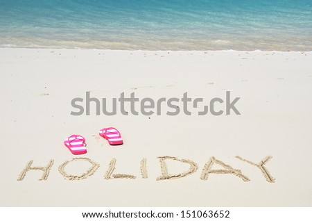 HOLIDAY writing on the sandy beach  - stock photo
