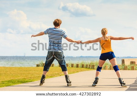 Holidays, active people and friendship concept. Young fit couple on roller skates riding outdoors on sea coast, woman and man rollerblading together on the promenade