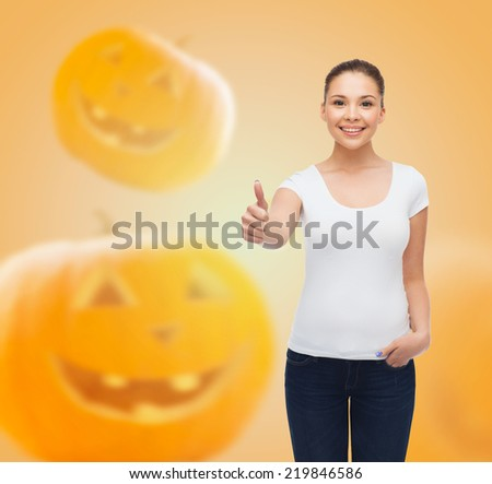 holidays, advertisement, gesture and people concept - smiling young woman in blank white t-shirt showing thumbs up over halloween pumpkins background - stock photo