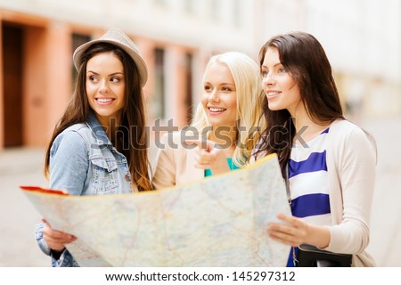 holidays and tourism concept - beautiful girls looking for direction in the city - stock photo