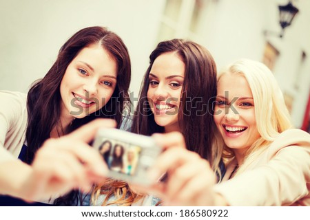 holidays and tourism concept - beautiful girls taking picture in the city - stock photo