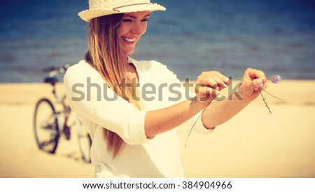 Holidays and vacation. Lovely cute woman tourist holding little flower on sunny beach. Young girl enjoy her free time on seaside. - stock photo