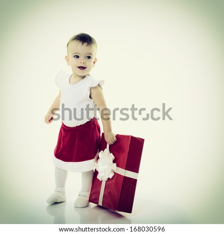 Holidays, baby girl holding a present, christmas, birthday, new year, x-mas concept - happy child girl with gift boxes  - stock photo
