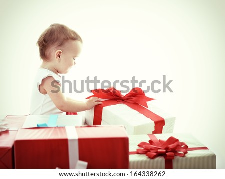 Holidays, baby girl opening box with presents, christmas, birthday, new year, x-mas concept - happy child girl with gift boxes, toned - stock photo