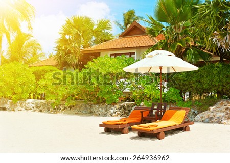 Holidays Background. Beach chairs on tropical white sand beach - stock photo