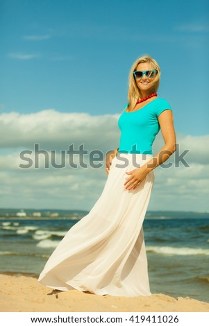 Holidays, beauty and summer fashion concept. Attractive blonde girl in full length walking on beach. Young woman relaxing on the sea shore.