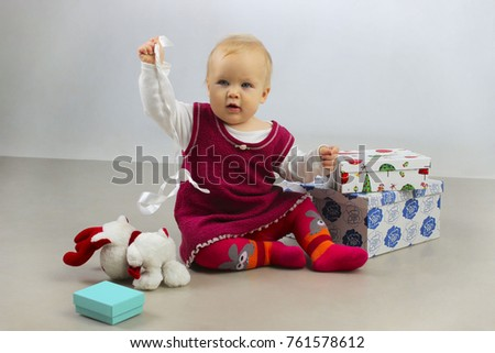 Holidays, Birthday, Children and people concept.Shot of a little adorable baby girl opening presents and playing toys. An Adorable Baby Girl in red dress playing with Christmas Gifts.