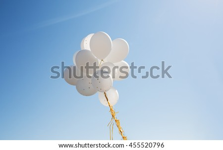 holidays, birthday, party and decoration concept - close up of inflated white helium balloons in blue sky - stock photo