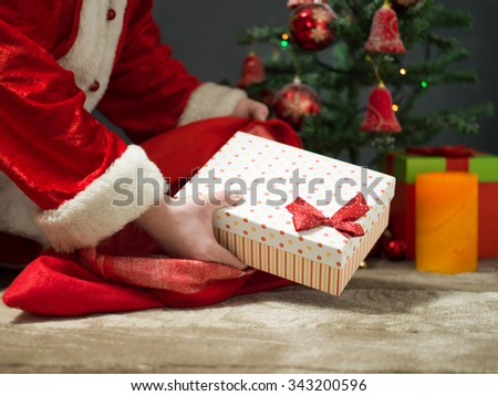 holidays, celebration and people concept - close up of santa claus putting present under christmas tree