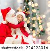 holidays, celebration, childhood and people concept - smiling little girl hugging with santa claus over christmas tree lights background - stock photo