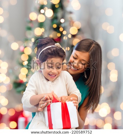 holidays, celebration, family and people concept - happy mother and little girl with gift box over living room and christmas tree background - stock photo
