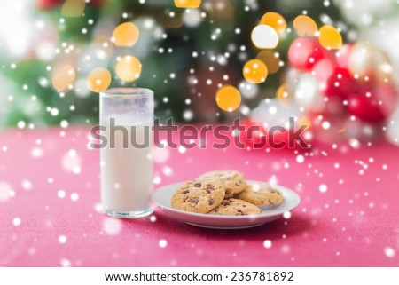 holidays, celebration, food, drinks and home concept - close up of cookies and milk glass on table over christmas tree and snow - stock photo
