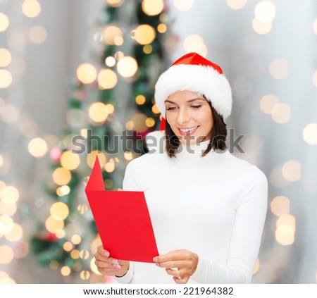 holidays, celebration, greeting and people concept - smiling woman in santa helper hat with greeting card over living room and christmas tree background - stock photo