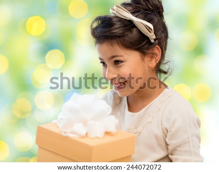 holidays, children, christmas, people and birthday concept - happy little girl with gift box over green lights background - stock photo