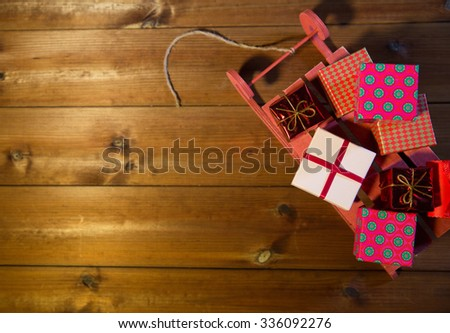 holidays, christmas, advertisement, new year and celebration concept - close up of many little gift boxes on red wooden sleigh on wooden board - stock photo