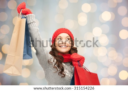 holidays, christmas, sale and people concept - happy young asian woman in winter clothes with shopping bags over lights background - stock photo