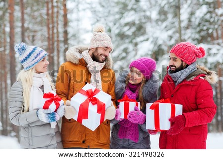 holidays, christmas, season, friendship and people concept - group of smiling friends with gift boxes in winter forest - stock photo