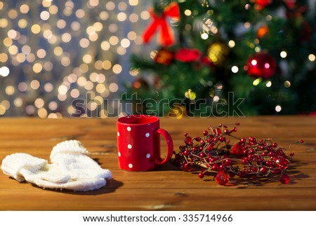holidays, christmas, winter and drinks concept - close up of tea cup with mittens and christmas decoration on wooden table - stock photo