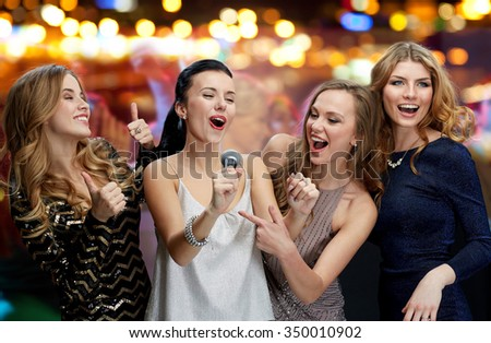 holidays, friends, bachelorette party, nightlife and people concept - three women in evening dresses with microphone singing karaoke over night club disco lights background - stock photo