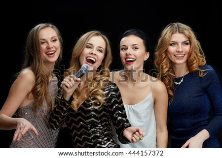 holidays, friends, bachelorette party, nightlife and people concept - three women in evening dresses with microphone singing karaoke over black background - stock photo