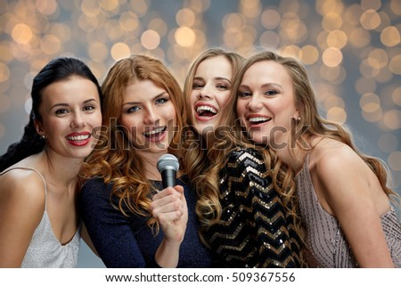 holidays, friends, bachelorette party, nightlife and people concept - three women in evening dresses with microphone singing karaoke over lights background