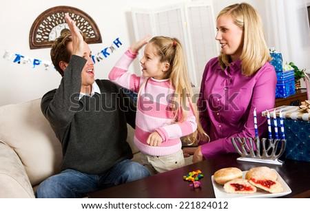 Holidays: Girl Gets High Five For Winning Dreidel Game - stock photo