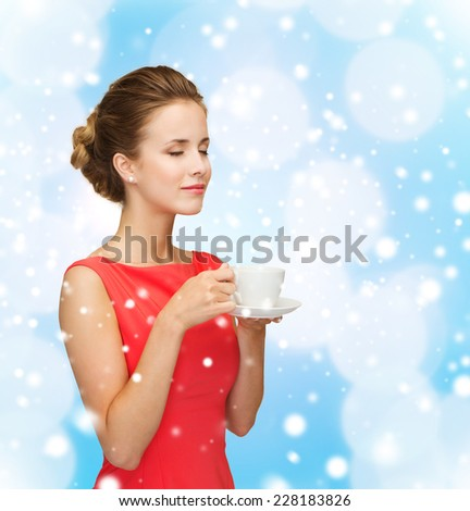holidays, happiness and drink concept - smiling woman in red dress with cup of coffee over blue lights background and snow - stock photo