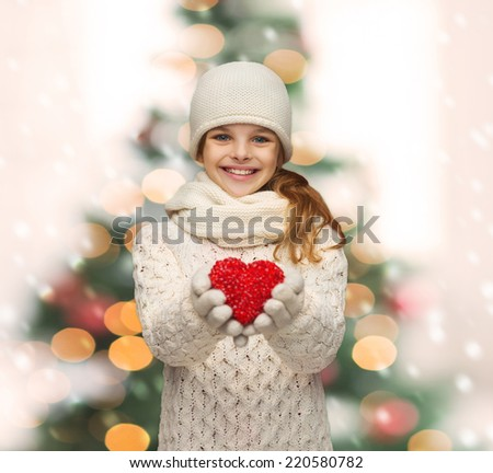 holidays, happiness, charity concept - smiling teenage girl in winter clothes with small red heart - stock photo