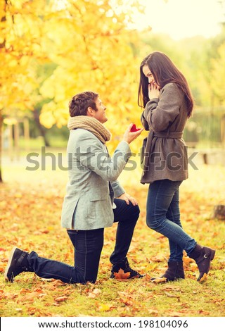 holidays, love, couple, relationship and dating concept - kneeled man proposing to a woman in the autumn park - stock photo