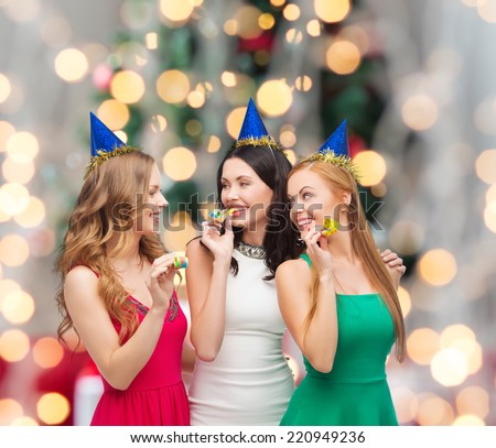 holidays, people and celebration concept - smiling women in party caps blowing to whistles over christmas tree lights background - stock photo