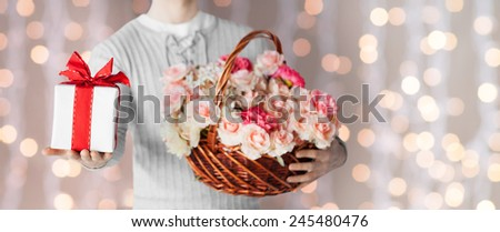 holidays, people, feelings and greetings concept - close up of man holding basket full of flowers and gift box over lights background - stock photo