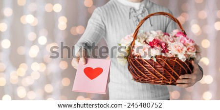 holidays, people, feelings and greetings concept - close up of man holding basket full of flowers and giving postcard over holidays lights background - stock photo