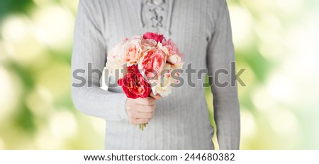 holidays, people, feelings and greetings concept - close up of man holding bunch of flowers over green background - stock photo