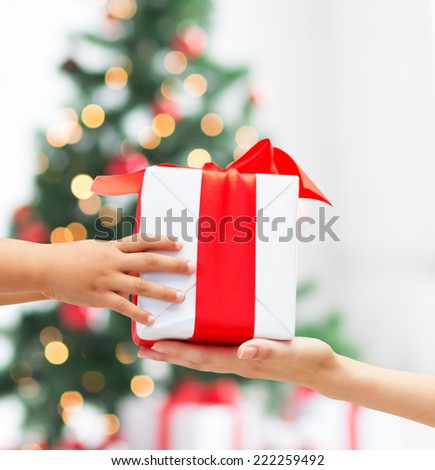 holidays, present, childhood and happiness concept - close up of child and mother hands with gift box over christmas tree lights background - stock photo
