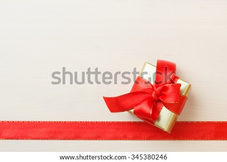 Holidays, present concept. Small golden box with gift tied decorative bow and red ribbon frame