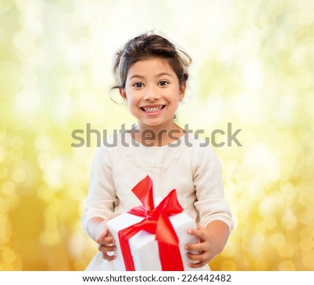 holidays, presents, christmas, childhood and people concept - smiling little girl girl with gift box over yellow lights background - stock photo