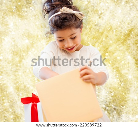 holidays, presents, christmas, childhood and people concept - smiling little girl with gift box over yellow lights background