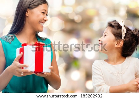 holidays, presents, christmas, family, child and x-mas concept - happy mother and child girl with gift box - stock photo