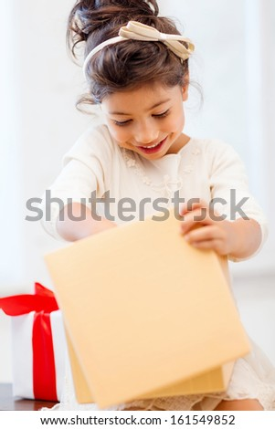 holidays, presents, christmas, x-mas, birthday concept - happy child girl with gift box - stock photo