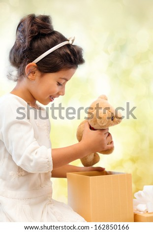 holidays, presents, christmas, x-mas, birthday concept - happy child girl with gift box and teddy bear - stock photo
