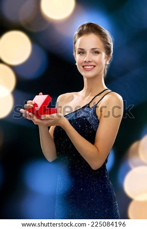 holidays, presents, luxury and happiness concept - smiling woman in dress holding red gift box night lights background - stock photo