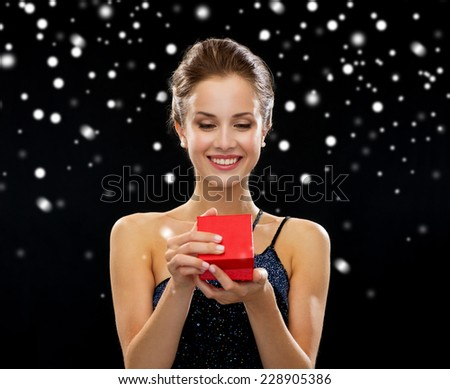 holidays, presents, luxury and happiness concept - smiling woman in dress holding red gift box over black snowy background - stock photo