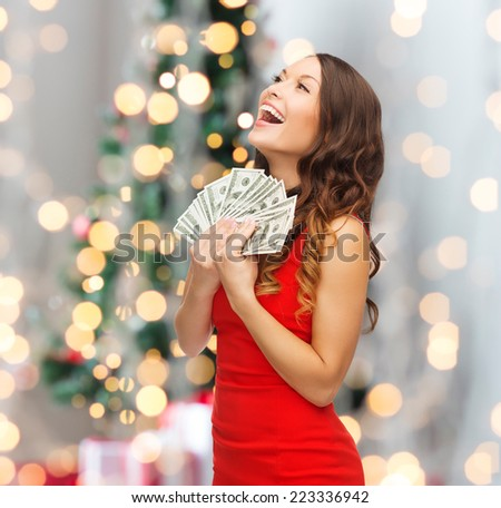 holidays, sale, banking and people concept - smiling woman in red dress with us dollar money over christmas tree lights background - stock photo