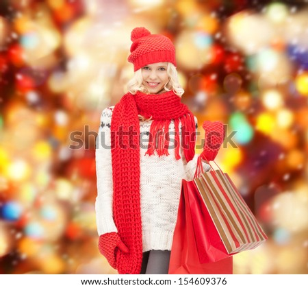 holidays, sale, christmas concept - beautiful teenage girl in winter clothes with shopping bags - stock photo