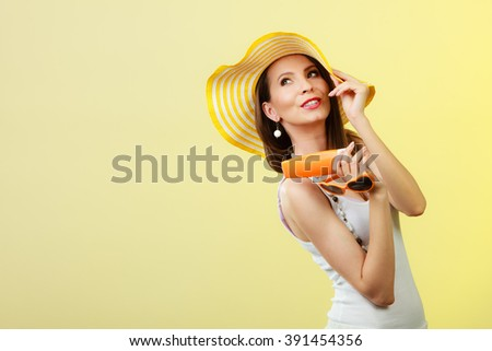 Holidays summer fashion. and skin care concept. Woman in yellow hat holds heart shaped sunglasses sunscreen lotion, bright background copy space