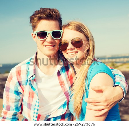 holidays, vacation, love and friendship concept - smiling couple having fun outdoors - stock photo