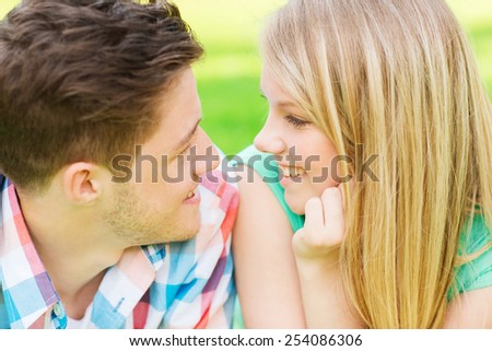 holidays, vacation, love and friendship concept - smiling couple looking at each other in park - stock photo