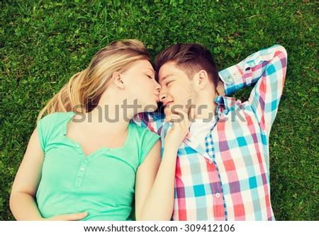 holidays, vacation, love and friendship concept - smiling couple lying on on grass and kissing in park - stock photo