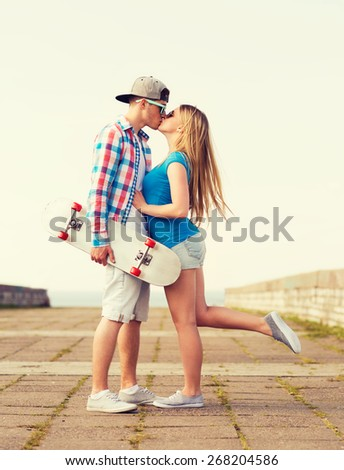 holidays, vacation, love and friendship concept - smiling couple with skateboard kissing outdoors - stock photo